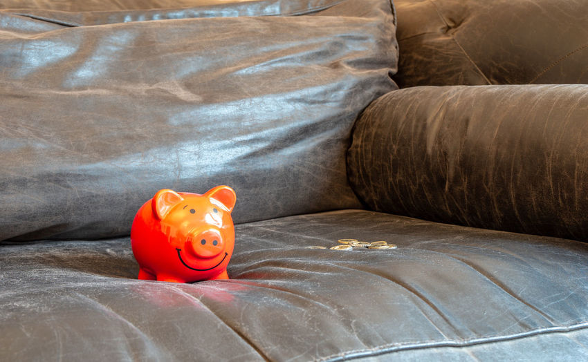 piggy bank on a couch Savings Investment Indoors  Furniture Wealth Sofa Piggy Bank Animal Representation Bed Domestic Room Single Object Home Interior Pillow Bedroom Finance Representation Relaxation No People Safety Business