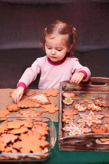 Girl Arranging Christmas Gingerbread Cookies In Wooden Tray At Home