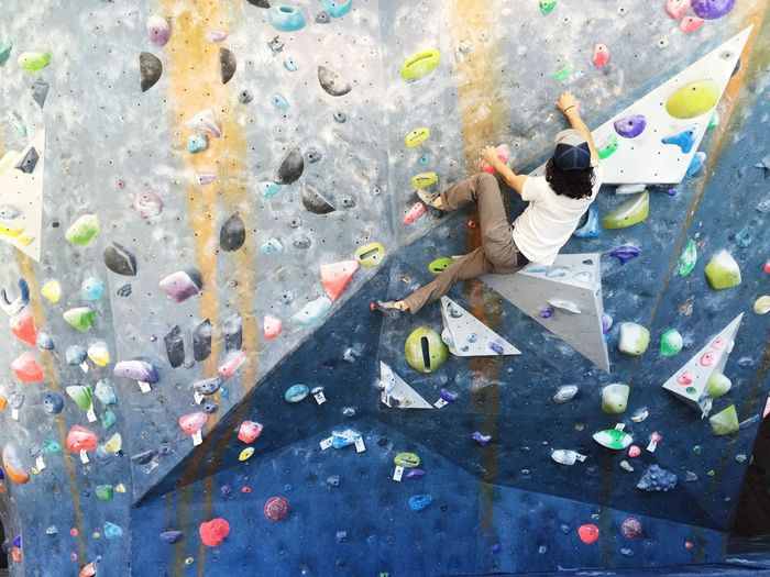 Rear view of man climbing wall