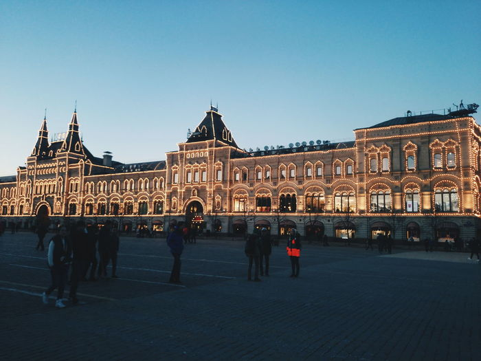 People at red square with illuminated gum against clear sky