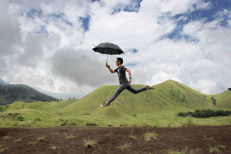 Side View Of Young Man With Umbrella Jumping By On Mountain Against Cloudy Sky