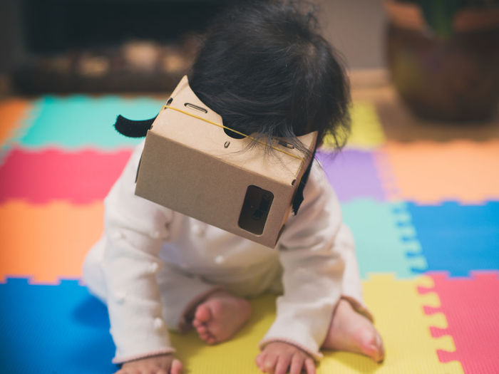 baby girl playing google cardboard goggle Baby Girl Black Hair Childhood Close-up Day Focus On Foreground Google Cardboard Indoors  Leisure Activity Lifestyles One Person Real People Toy Visual Reality