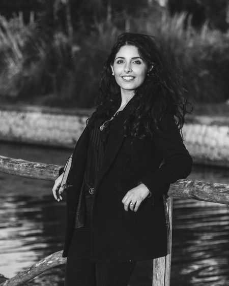 Portrait of smiling young woman leaning on railing by river