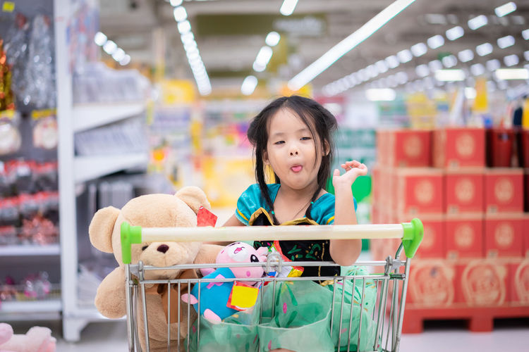 Cute girl sticking out tongue while sitting in shopping cart at store