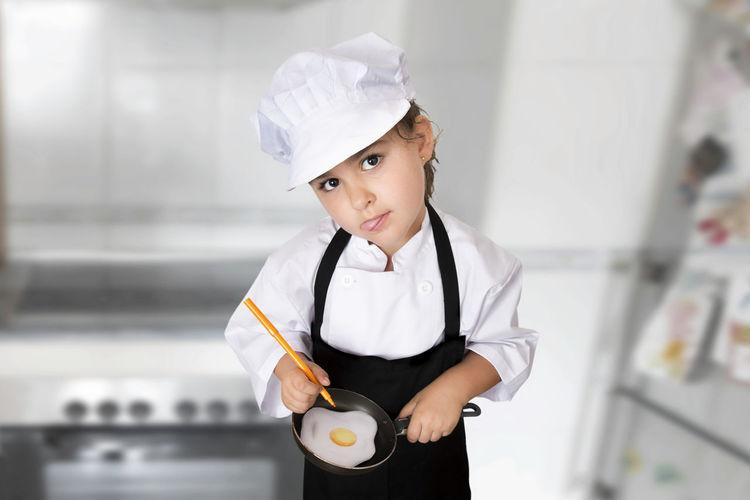 Portrait Of Girl In Chef Uniform Preparing Fried Egg In Kitchen