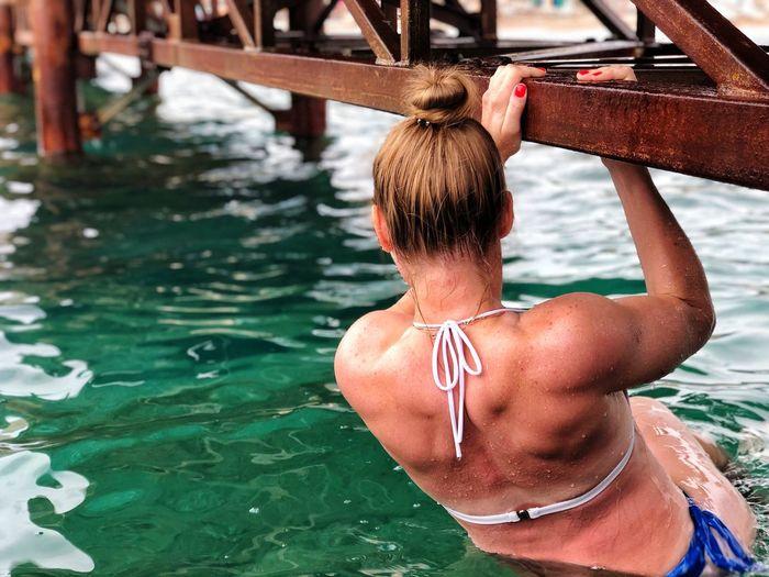Rear view of woman in bikini swimming pool