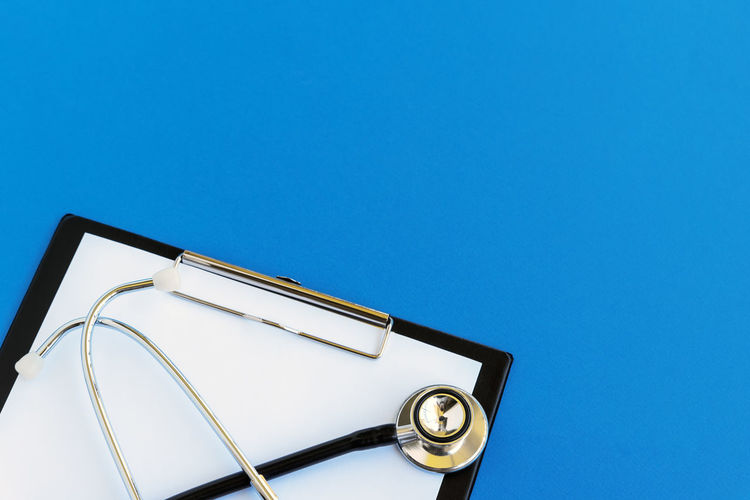 Blue Copy Space Blue Background Stethoscope  Clipboard Medical Exam Medical Equipment Still Life Studio Shot Medicare Healthcare And Medicine