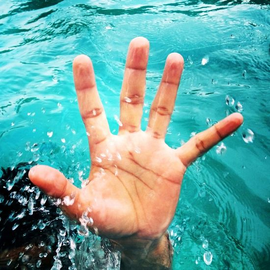 Close-up of hand on water in swimming pool