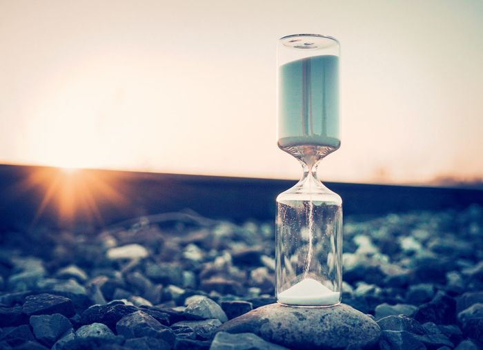 Close-up of hourglass on railroad track during sunset