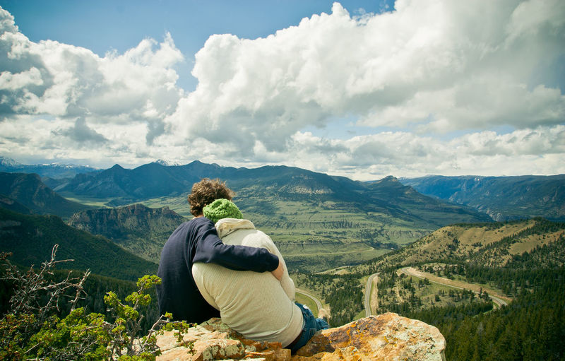 Rear view of man sitting on mountain