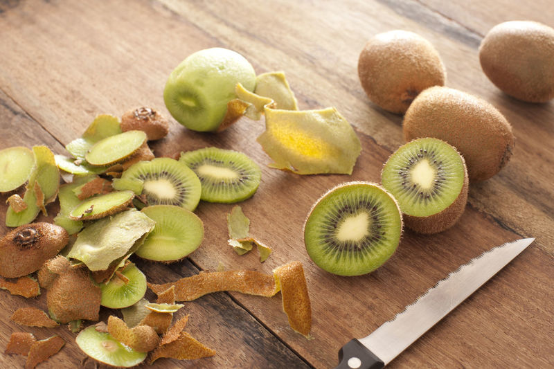 High Angle View Of Kiwis And Knife On Cutting Board