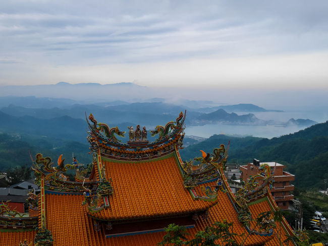 Traditional Chinese style roof in yellow with misty landscape hillside and seaview of the ocean Roof Taiwan Architecture Beauty In Nature Belief Building Building Exterior Chinese Cloud - Sky Jiufen Mist Mountain Nature Ornate Outdoors Place Of Worship Religion Shrine Sky Spirituality Temple Traditional Travel Travel Destinations Yellow