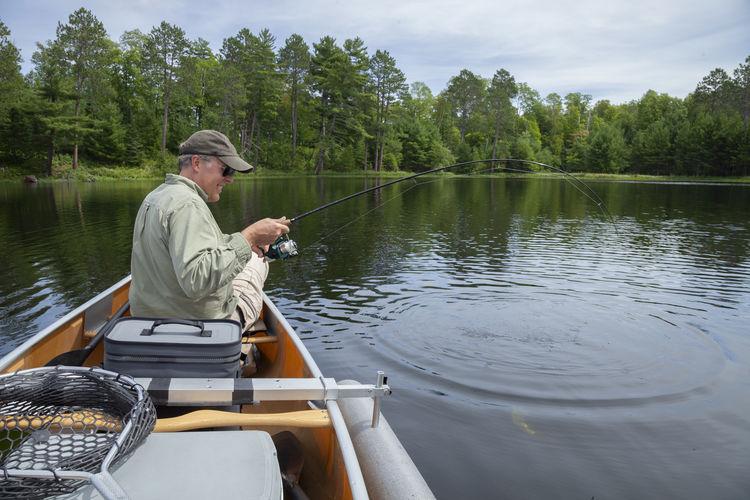 Smiling man sitting on boat fishing in lake