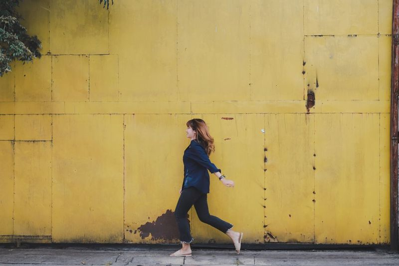 Full length of woman on sidewalk against yellow wall