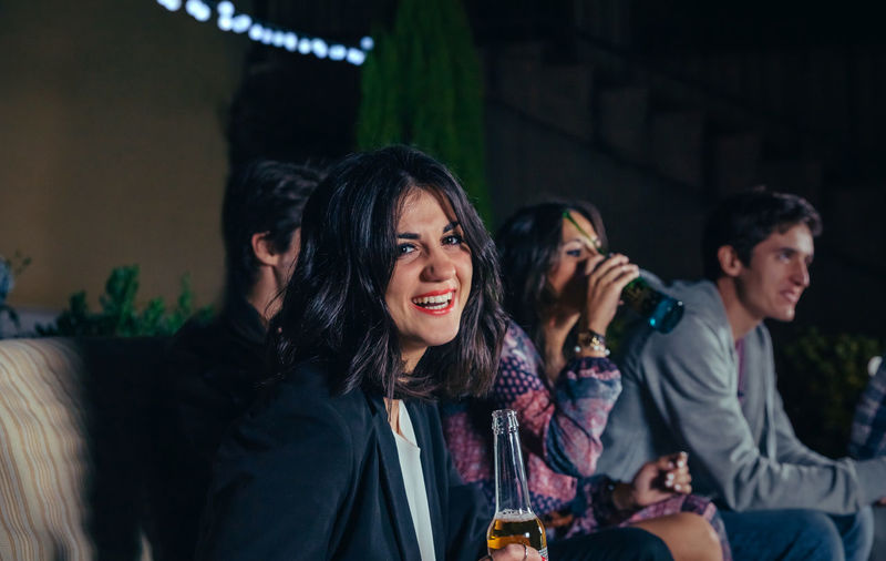 Portrait of smiling young woman sitting and holding a beer while her friends talking in a outdoors party. Friendship and celebrations concept. Beer Celebration Friends Fun Happiness Happy Horizontal Laughing Light Young Alcohol Bottle Cheerful Drink Entertainment Four People Friendship Group Night Nightlife Outdoors Party People Smiling Sofa
