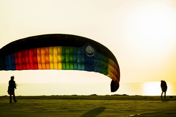 People Standing By Parachute Against Sea During Sunset