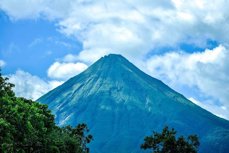 Magnificent Titan. Sky Cloud - Sky Beauty In Nature Nature Low Angle View Tranquility Tree Day Scenics Tranquil Scene No People Outdoors Mountain Green Color Growth Volcano Arenal  Arenal Volcano National Park Costa Rica Arenal Volcano National Park