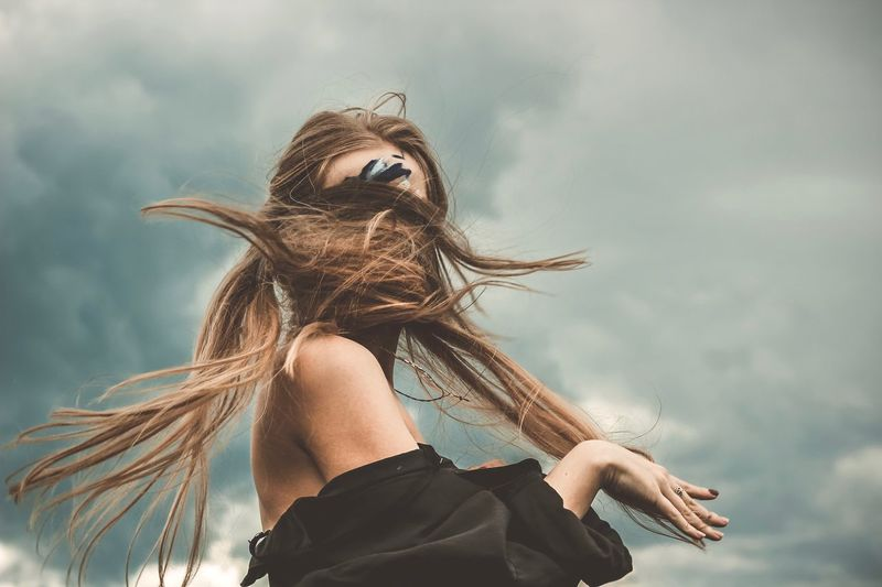 Woman With Tousled Hair Against Cloudy Sky