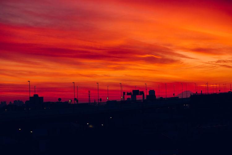 Silhouette of factory against orange sky