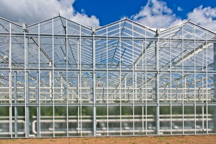 Metallic structure in greenhouse against sky