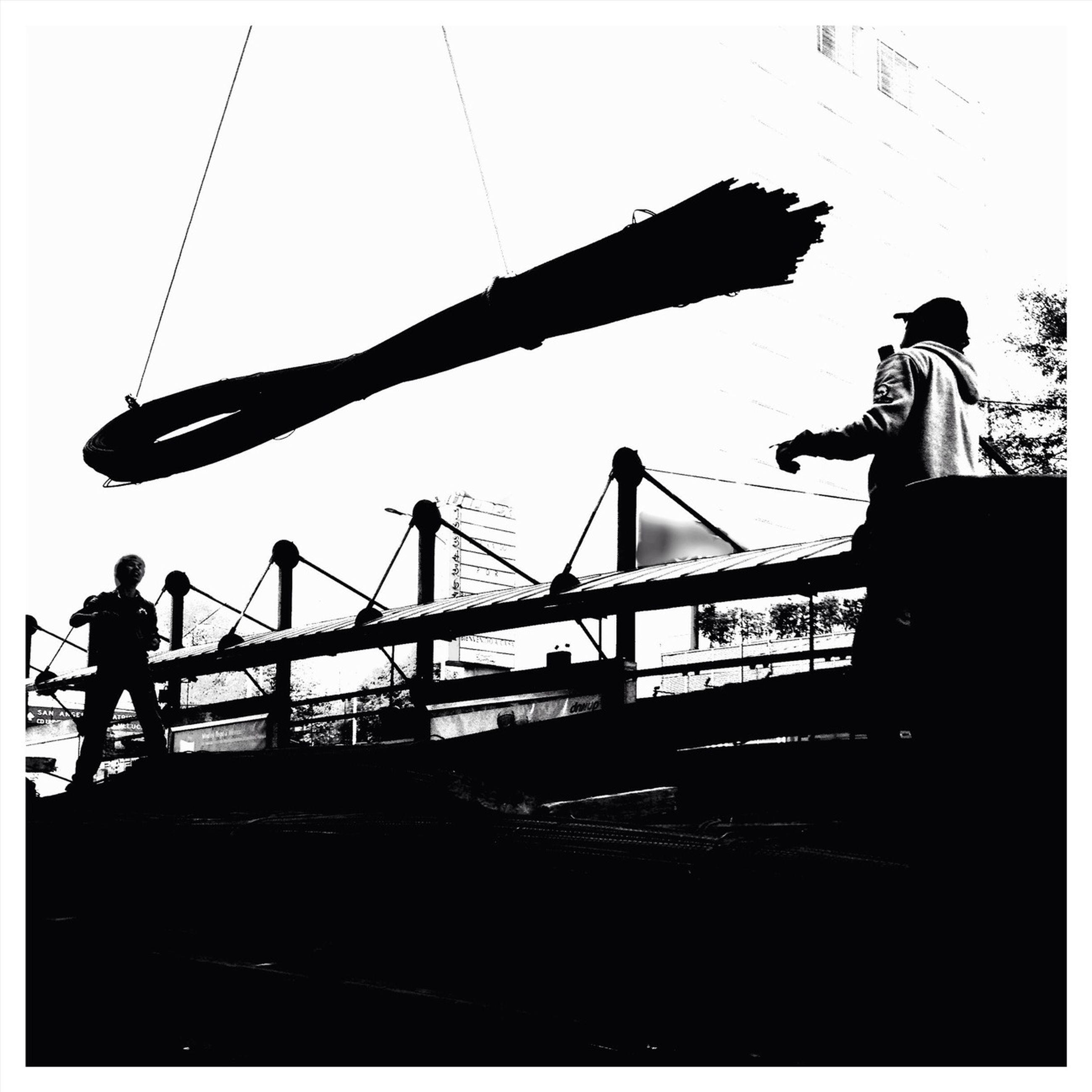 low angle view, built structure, silhouette, architecture, connection, construction site, sky, bridge - man made structure, crane - construction machinery, clear sky, outdoors, building exterior, sunset, transportation, railing, dusk, development, engineering, copy space, construction