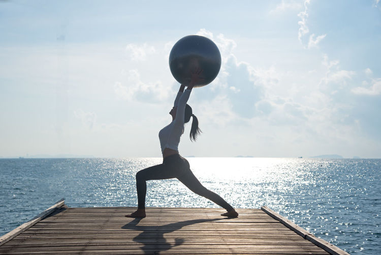 Water Sky Sea Lifestyles One Person Sport Real People Leisure Activity Nature Full Length Beauty In Nature Horizon Day Horizon Over Water Pier Healthy Lifestyle Wellbeing Exercising Yoga Outdoors Arms Raised Physical Activity Yoga Healthy Relax Pose Balance Ball