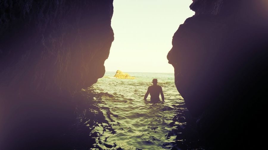 Rear View Of Silhouette Man Amidst Rocks In Sea