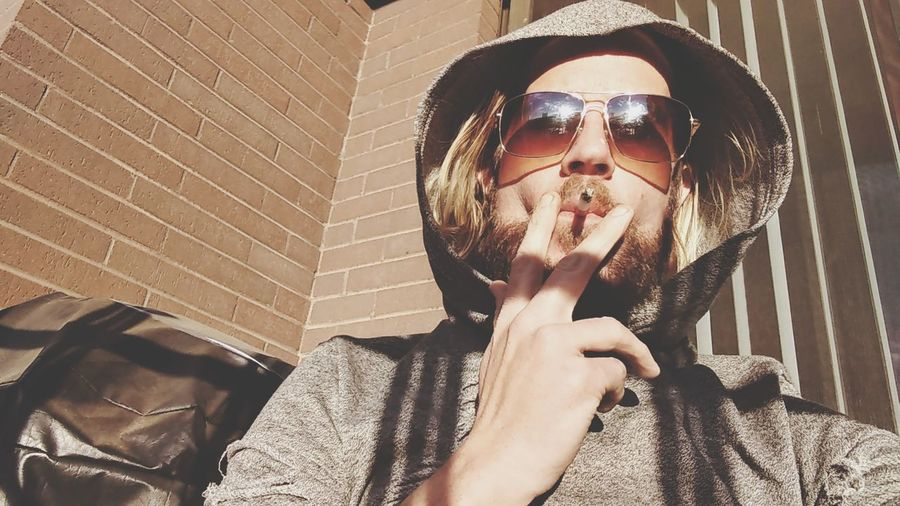 Portrait of man wearing sunglasses and hooded shirt smoking cigarette at home