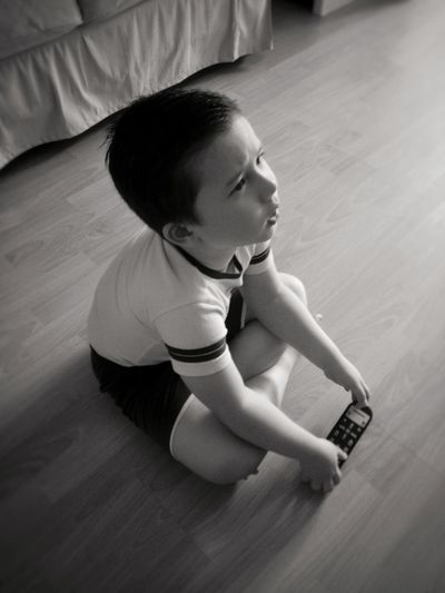 Cute boy with remote control looking away while sitting on floor
