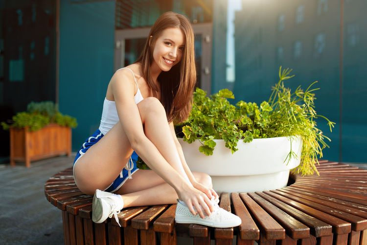 Young beautiful athletic girl with a beautiful figure after a morning jog Young Adult Young Women One Person Beauty Long Hair Smiling Real People Brown Hair Women Beautiful Woman Hairstyle Sitting Portrait Adult Looking At Camera Hair Lifestyles Day Casual Clothing Outdoors Resting Sport Sexygirl Morning Running