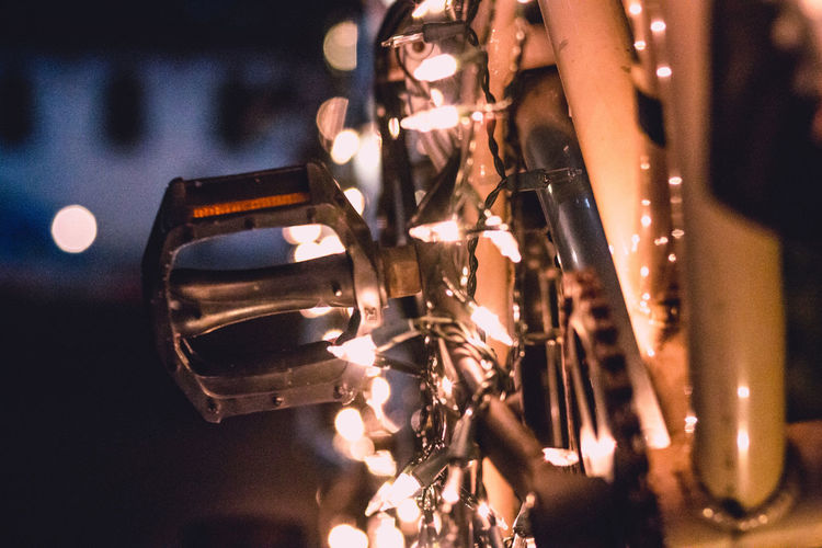 Close-up of illuminated string lights on bicycle at night