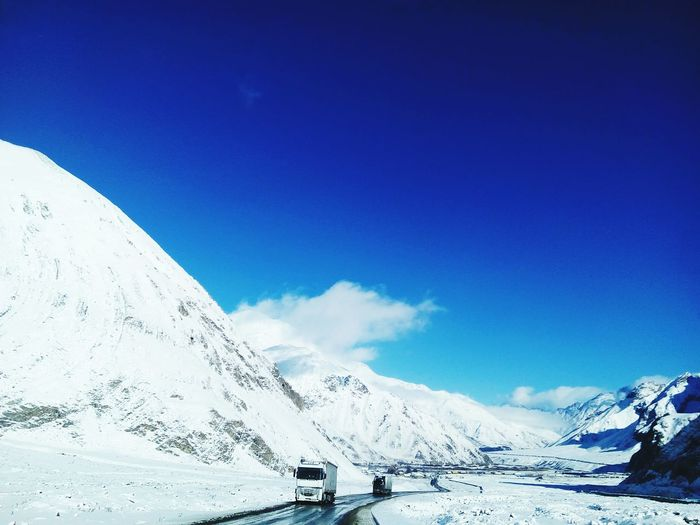 On the way to Kazbegi Truck Way Ahead Valley Road Mountain Snow Cold Temperature Winter Road Snowcapped Mountain Road Trip Blue Car Winding Road