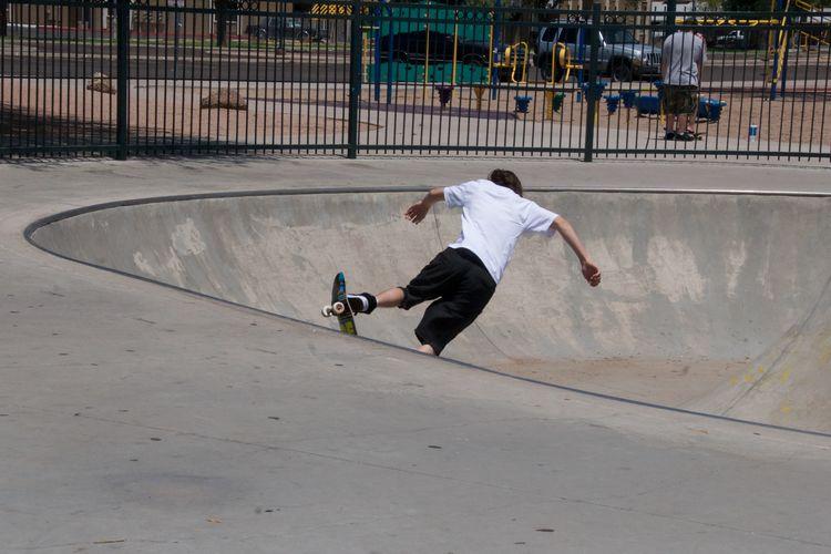 Rear view of man skateboarding on skateboard park