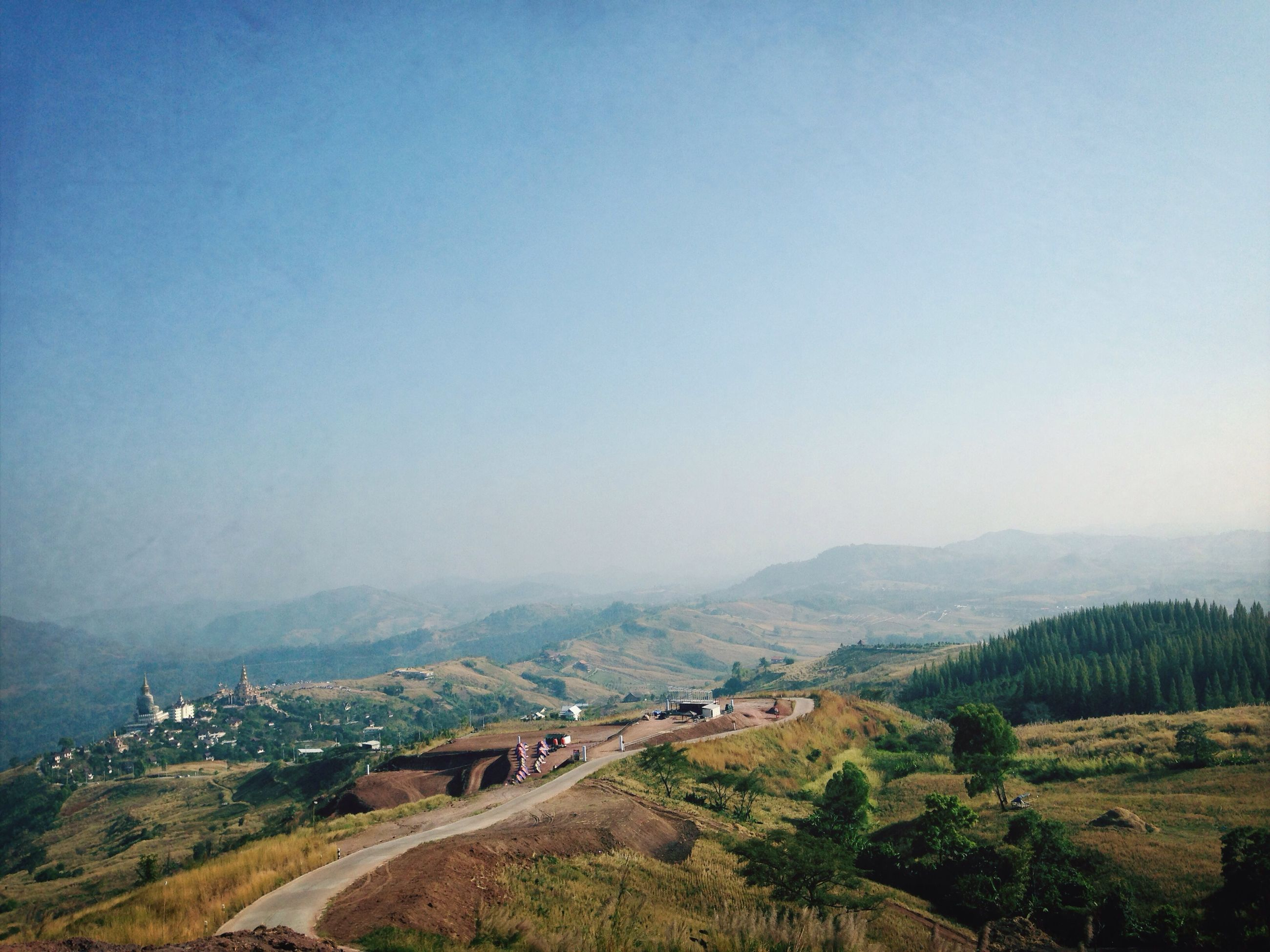 mountain, copy space, clear sky, landscape, scenics, tranquility, tranquil scene, mountain range, high angle view, tree, beauty in nature, nature, non-urban scene, built structure, hill, outdoors, day, blue, road