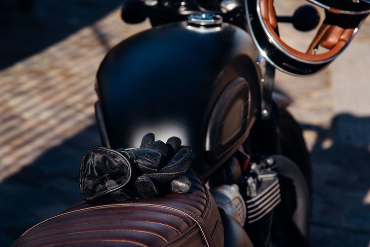 Close-up of gloves on motorcycle parked outdoors