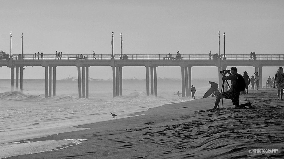 Capturing Sunset in a Kneeling position. Beach Sea Leisure Activity Lifestyles Pier Water Tourism Shore Wave Tranquil Scene Blackandwhite Orange County California Coast Huntington Beach Beach Photography Beach Life Jnphotography Eyeemphotography HBSunsets