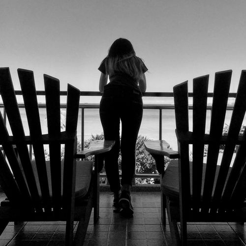 Rear view full length of woman standing against sea at balcony