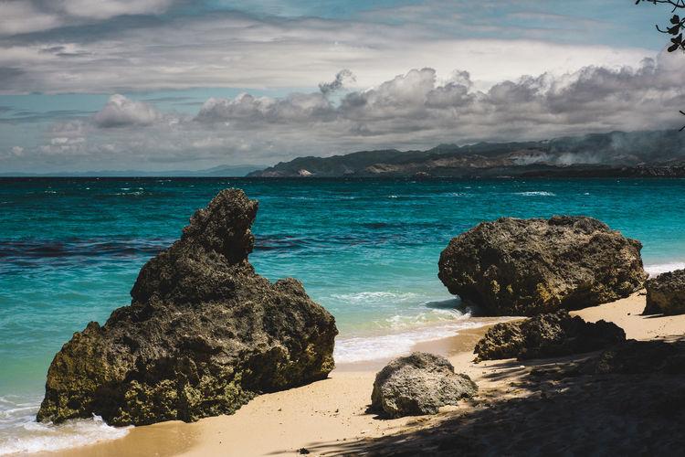 Rocks on sea shore against sky