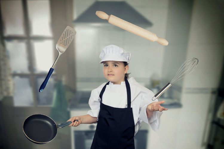 Girl in chef whites playing with cooking utensils