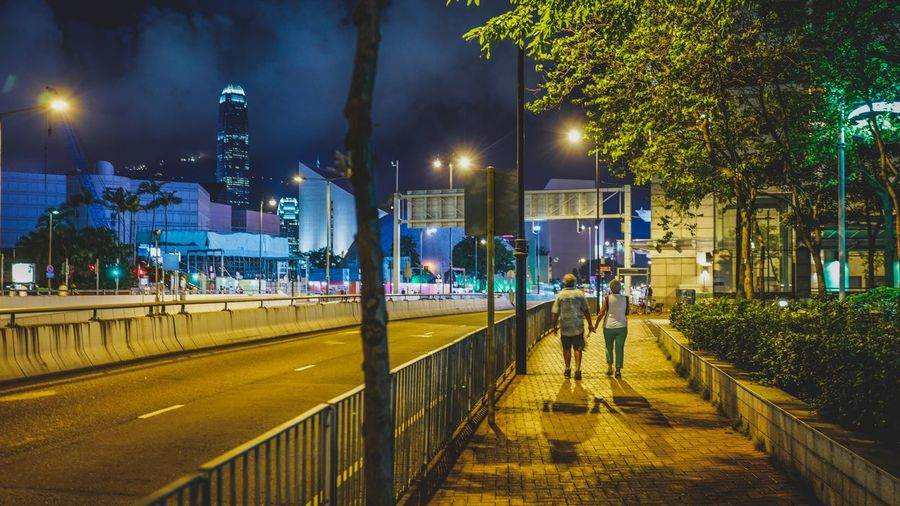 Rear view of couple walking on sidewalk at night