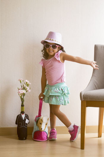 Full Length Of Cute Girl Wearing Hat Playing At Home