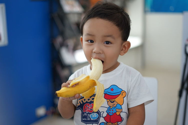 Close-up of cute boy eating banana