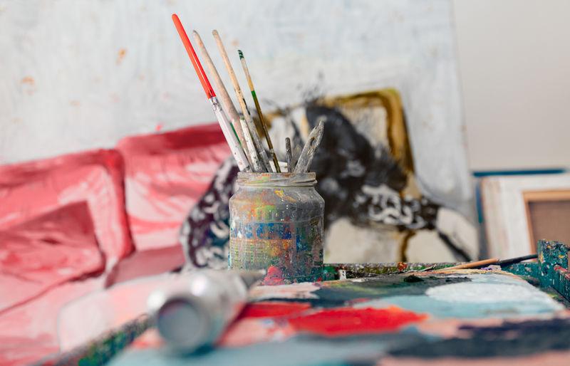 Painter workplace indoor at workshop atelier studio - focus on brushes