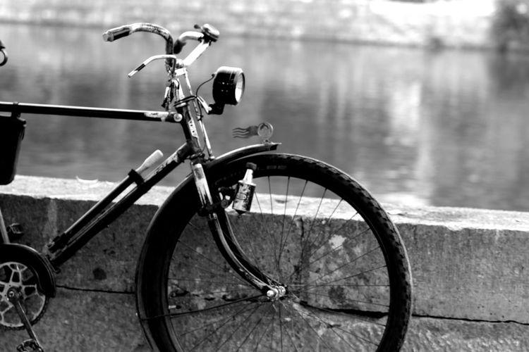 Bicycle parked by railing against lake