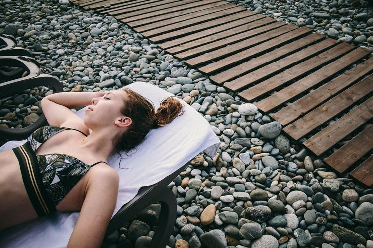 One Person Real People Leisure Activity Solid Lifestyles Young Adult Stone - Object Rock Young Women High Angle View Lying Down Day Three Quarter Length Nature Adult Women Relaxation Stone Pebble Outdoors Beautiful Woman Hairstyle Russia Beach Sochi