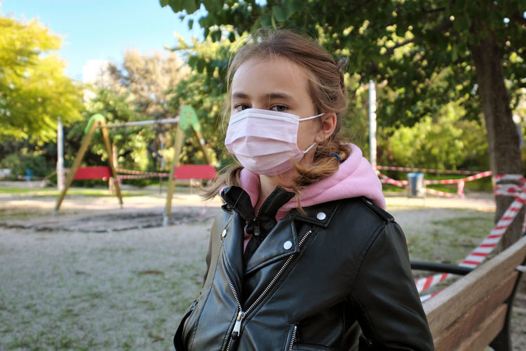 Portrait of girl wearing mask at park