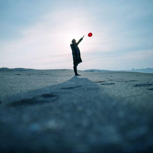 Full length of man releasing balloon on beach