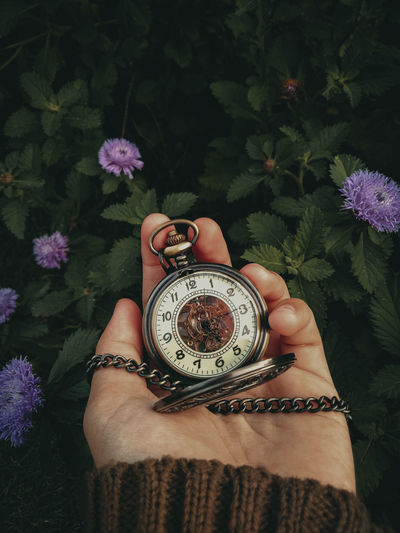 Close-up of hand holding vintage clock