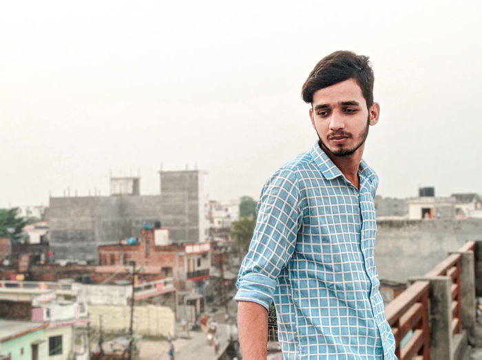 Portrait of young man standing against cityscape