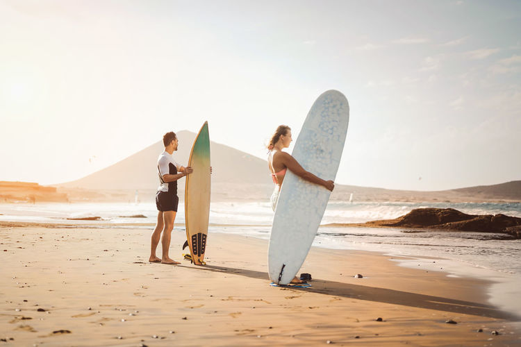 Man and woman standing with surfboard on beach against sea and sky